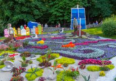 A large decorative flower bed of their flowers in the form of the sea with fish, mermaids, ships and other marine life. For your design stock image