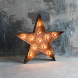 Large decorative retro star with lots of burning lights on grunge concrete background. Beautiful decor, modern design Stock Images