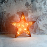 Large decorative retro star with lots of burning lights on grunge concrete background. Beautiful decor, modern design. Element. The loft style studio Royalty Free Stock Photography