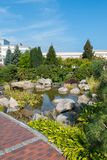 Large decorative stones in a small pond in a park among green bushes. For your design stock photo