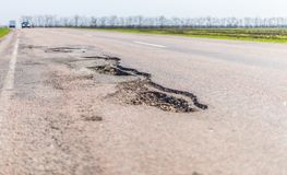 Large deep pothole an example of poor road stock photo