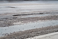 Large deep pothole. Of poor road maintenance due to cutbacks on the infrastructure budget Royalty Free Stock Image