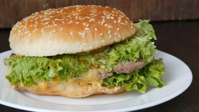 A large delicious juicy burger with triple cutlet, fresh lettuce leaf and cheese lies on a white plate on a stylish. Large delicious juicy burger with triple stock video footage