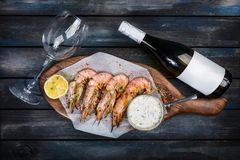 Large delicious shrimp or langoustine with white sauce, bottle of wine, glass for the wine and half a lemon on a wooden. Board. Top view Royalty Free Stock Photo