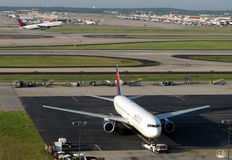 Delta planes at atlanta harstfield jackson airport. A large Delta jet is towed by a plane tractor as another large delta jet takes off in the background at Stock Photography