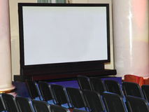 A large demonstration plasma screen and rows of seats for spectators. Stock Photo