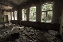 A large destroyed hall in a kindergarten in Chernobyl: garbage on the floor, inverted furniture, torn wallpaper, dusk in the room, Royalty Free Stock Image