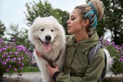 Large detailed horizontal portrait of a young stylish girl with dreadlocks and her white Samoyed dog. With a caring expression she`s holding the dog and Royalty Free Stock Photography