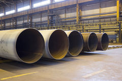 Large diameter pipes are stacked in an industrial factory shop Stock Photo
