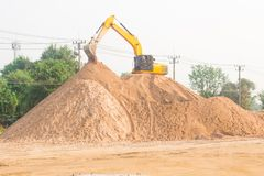 Large diesel mechanical excavator digging earth machine at excavation working in road construction.  stock photo