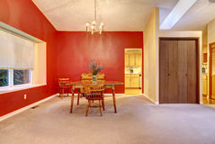Large dining room with red wall and small wood table. Royalty Free Stock Images