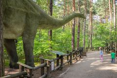 Large Diplodocus in dinosaur park. Little children looking at the massive replica of the gigantic Diplodocus dinosaur in an amusement park in Solec Kujawski Stock Photo