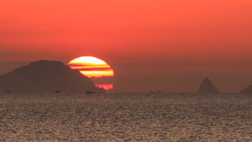 Large disk of sun appears from behind hill sea at foreground stock video footage