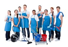 Large diverse group of janitors with equipment. Large diverse group of janitors wearing blue aprons standing grouped together with their equipment smiling at the stock images