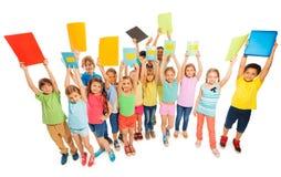 Large diverse group of kids lifting up textbooks stock photos