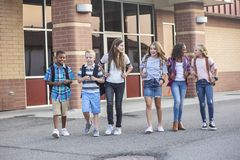 Free Large, Diverse Group Of Kids Leaving School At The End Of The Day. School Friends Walking Together And Talking Together On Their W Royalty Free Stock Image - 155425956