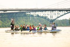 Large diverse group of people rowing on large kayak. stock image