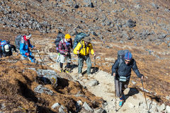 Large Diverse Group of People walking up on rocky Trail Stock Photo