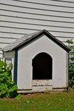 Large Dog House in White. A large white dog house is located against a house of white siding Royalty Free Stock Images