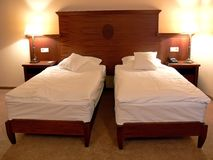 Large double bed. A view of a unique double bed consisting of two twin beds, separated by several inches but sharing the same large wooden headboard Stock Photo