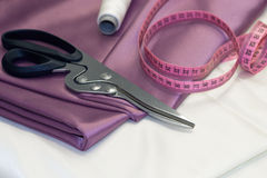 Large dressmaking scissors and pink measuring tape Royalty Free Stock Image
