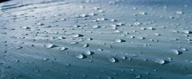 Large drops of water on Cyan textiles with a waterproof effect. Water-repellent impregnation. Texture drops on the fabric. Selective focus stock images