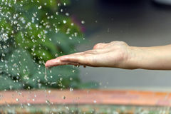 Hand under the water drops. Large drops of water flying on the female hand Stock Images