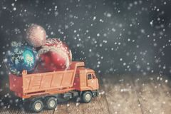 A large dump truck carries Christmas balls during blizzards and snowfall. The concept of delivery of Christmas gifts and goods in all weather conditions royalty free stock images