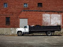 Large Dumptruck and Brick Building Royalty Free Stock Photos