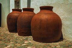 Large earthenware vessels over floor. Close-up of large earthenware vessels over deserted floor and rough plaster wall at Campo Maior. A cute little town with royalty free stock photo