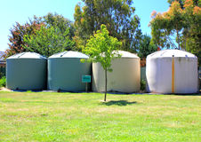Large eco- friendly water storage tanks. Large eco- friendly fresh water storage tanks in suburban backyard Stock Images