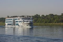Large egyptian river cruise boat sailing on Nile. Large luxury traditional Egyptian river cruise boat sailing on the Nile with reflection stock photo