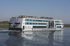 Large egyptian river cruise boat sailing on Nile. Large luxury traditional Egyptian river cruise boat sailing on the Nile with reflection royalty free stock photography