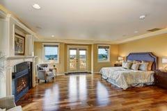 Large elegant master bedroom with fireplace. Stock Photo