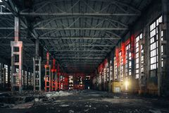 Large empty abandoned warehouse building or factory workshop, abstract ruins background. Toned stock photo
