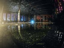 Large empty abandoned warehouse building or factory workshop at night with reflection in water, abstract ruins background royalty free stock image