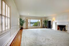 Large empty living room with fireplace and lake view. stock photo