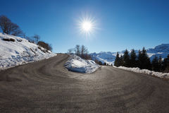 Large empty mountain road curve on Alps with snow on sides Royalty Free Stock Photo