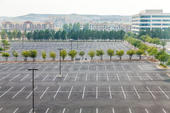 Large Empty Parking Lot with One White Car. Empty parking lot with one white car in distance Royalty Free Stock Image