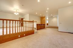 Large empty room with beige carpet and railing. Royalty Free Stock Photo