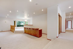 Large empty room with beige carpet, wooden bar and railing. Large empty room with beige carpet, wooden bar, white walls and railing stock photography