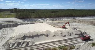 Tip truck drives to excavator at sand quarry upper view