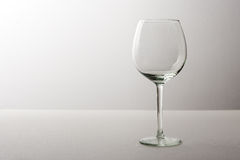 Large empty transparent glass glass of wine standing on a gray background Stock Photos