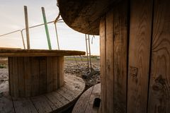 Large empty Wooden Coil - Wooden Spool - Wooden Bobbins in a construction yard against a bright sunset stock image