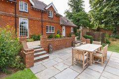 Large English house and garden. Large historic Victorian house featuring an English garden and patio with wooden furniture. Buckinghamshire, UK stock photo