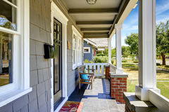 Large entance porch with brick trim and white railings. Clapboard siding house exterior. Large entance porch with brick trim and white railings. Old wooden bench Stock Images