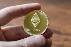 A Large Etherium Token in hand. A gold Etherium token in hand stock photos