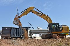 A large excavator dumps dirt into a truck royalty free stock photography