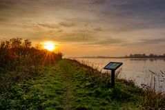 Sunset over a large nature reserve and wetland area seen in winter. The large expanse of water is home to many migrating birds and wildfowl and is in a protected Stock Photo