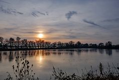 Sunset over a large nature reserve and wetland area seen in winter. The large expanse of water is home to many migrating birds and wildfowl and is in a protected Royalty Free Stock Photography